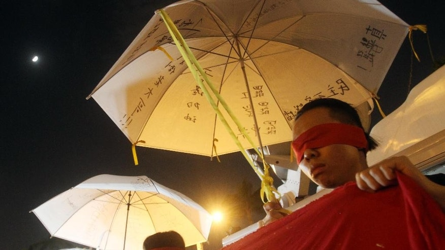 Demonstrators cover their eyes and hold a slogan to support pro-democracy protests taking place in Hong Kong at the Liberty Square in front of Chiang Kai-shek Memorial Hall in Taipei, Taiwan, Wednesday, Oct. 1, 2014. (AP Photo/Chiang Ying-ying)