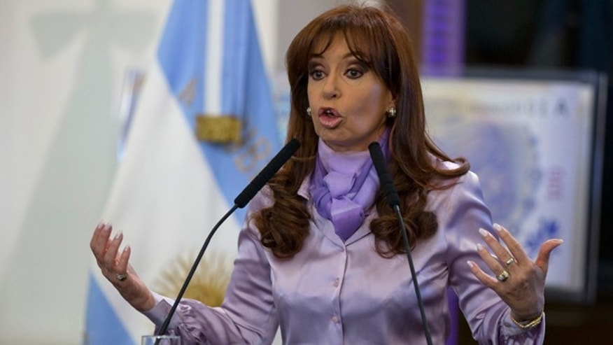 Argentina's President Cristina Fernandez talks inside the government house in Buenos Aires, Argentina, Tuesday, Sept. 30, 2014. Argentina deposited a $161 million bond interest payment with a newly appointed local trustee on Tuesday in defiance of a U.S. judge who held it in contempt a day earlier for attempting illegal moves to service its debt. The move aims to prove that Argentina can meet its debt locally and sidestep a U.S. court ruling that recently pushed it into its second default in 13 years.  (AP Photo/Natacha Pisarenko)