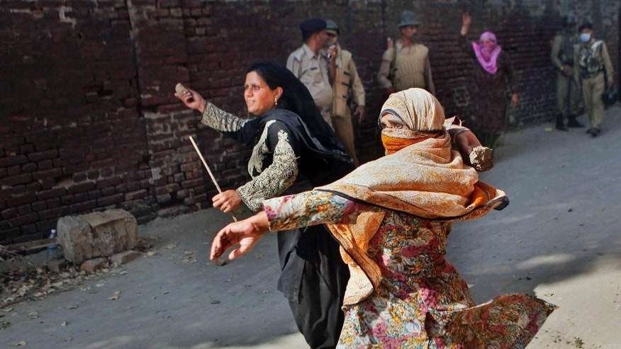 In this Wednesday, Oct. 1, 2014 photo, Kashmiri Muslim anti-government protesters hurl bricks and stones at Indian policemen during a protest in Srinagar, India. Flooding in this conflict-wracked Himalayan region in early September has killed 281 people, destroyed at least 100,000 homes and caused an estimated $17 billion in damage. Anger flared within days after the floods over what they view as a woefully inadequate government response is reviving calls for independence, tapping decades of animosity that fueled a 25-year separatist battle and an Indian military crackdown that left tens of thousands dead in the mostly Muslim region. (AP Photo/Dar Yasin)