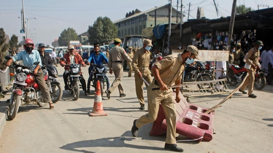 In this Wednesday, Oct. 1, 2014 photo, Indian policemen remove road blocks set by protesters in Srinagar, India. Anger flared within days after floods in the Himalayan region in early September killing 281 people, destroying at least 100,000 homes and causing an estimated $17 billion in damage. Kashmiris' fury over what they view as a woefully inadequate government response is reviving calls for independence, tapping decades of animosity that fueled a 25-year separatist battle and an Indian military crackdown that left tens of thousands dead in the mostly Muslim region. (AP Photo/Dar Yasin)
