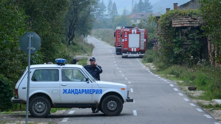 Police and firefighters trucks are seen on the road that leads to an ammunition factory in the village of Gorni Lom, some 120 kms, 75 miles north of the capital  Sofia, Thursday, Oct. 2, 2014.  Fifteen people were confirmed dead in a blast at the explosives decommissioning factory in Gorni Lom Bulgaria. Civil Defense chief Nikolai Nikolov said Thursday that thirteen men and two women perished in the wake of the blast that left craters.  The explosion occurred  late Wednesday and police said smaller explosions continued for several hours. (AP Photo)