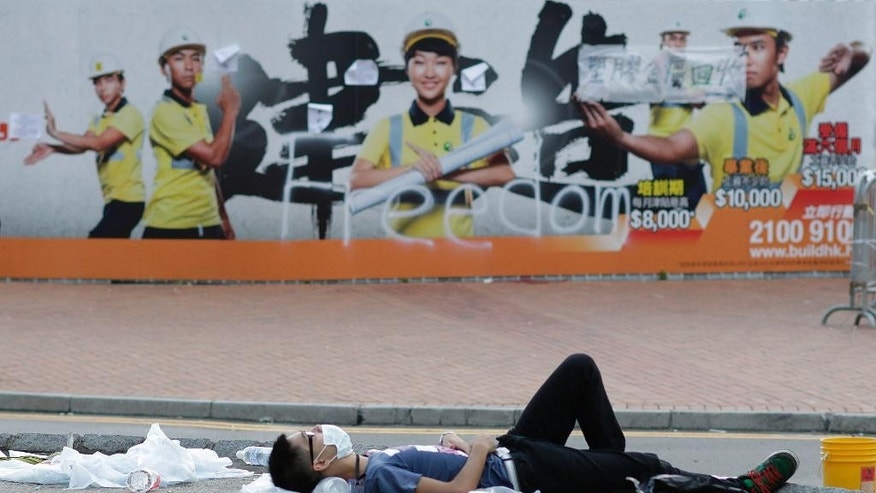 A lone pro-democracy student protester sleeps on an occupied main street outside of the government complex in Hong Kong, Thursday, Oct. 2, 2014. Raising the stakes in their standoff with the authorities, Hong Kong's pro-democracy protesters threatened to occupy key government buildings unless the territory's top official resigns by the end of the day Thursday. (AP Photo/Wally Santana)