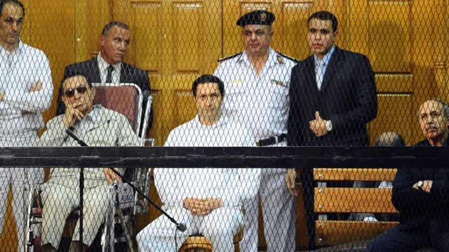 Sept. 14, 2013: Former Egyptian President Hosni Mubarak, seated in wheelchair, and his two sons, Gamal Mubarak, left, and Alaa Mubarak, fourth left, former Interior Minister Habib el-Adly, second right, and former head of Cairo security, Ismail al-Shaar, right, attend a hearing in a courtroom at the Police Academy