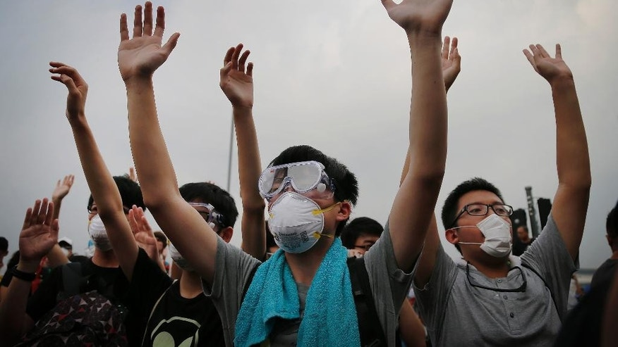 Student protesters raise their hands to show their non-violent intentions as they resist during change of shift for local police but backed down after being reassured they could reoccupy the pavement outside the government compound's gate, Thursday, Oct. 2, 2014 in Hong Kong. Hong Kong police warned of serious consequences if pro-democracy protesters try to occupy government buildings, as they have threatened to do if the territory's leader doesn't resign by Thursday. (AP Photo/Wong Maye-E)