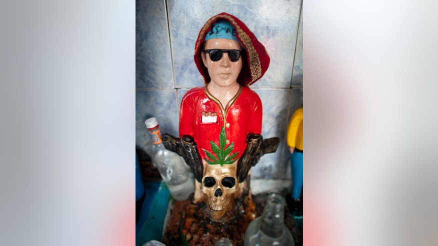 "In this Sept. 28, 2014 photo, a statue of Ismael stands at the pantheon of ""Santos Malandros,"" or Holy Thugs at the General Cemetery in the Guarataro slum in Caracas, Venezuela. Believers gather in the cemetery , sometimes by the dozens, kneeling in prayer, drinking liquor and smoking cigarettes as offerings to the small statue of the long-dead robber Ismael. The rising popularity of the cult has brought a proliferation of shops selling statuettes representing Santos Malandros, figures brandishing firearms and knives, or wearing sunglasses, jeans and colorful shirts. (AP Photo/Ariana Cubillos)"
