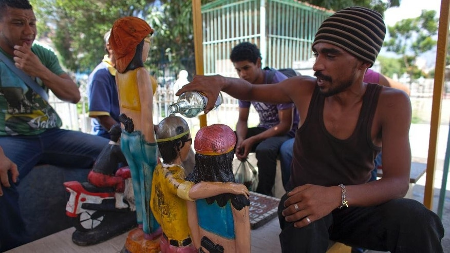 "In this Sept. 28, 2014 photo, Ivan, a believer makes an offering as he pours alcohol over the statues of Ismael and Elizabeth who was the girlfriend of Ismael at the pantheon of ""Santos Malandros,"" or Holy Thugs at the General Cemetery in the Guarataro slum in Caracas, Venezuela. Many people believe Ismael killed dozens of people while robbing banks and cargo trucks in the 1970s, before he was shot down by police. These days, the faithful revere him as a sort of Robin Hood, saying he stole from the rich and protects those among the poor who are besieged by crime. (AP Photo/Ariana Cubillos)"