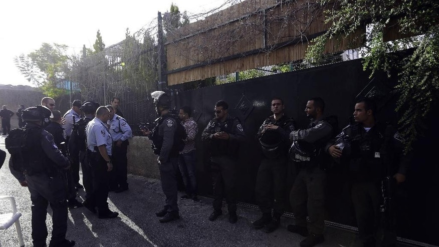 In this photo taken Tuesday, Sept. 30, 2014, Israeli police officers guard the house of Ziad Qarain, that Jewish settlers moved into, at the Palestinian neighborhood of Silwan, East Jerusalem. The settlers say the home has been legally purchased, while Palestinian residents claim such sales are fraudulent. (AP Photo/Mahmoud Illean)