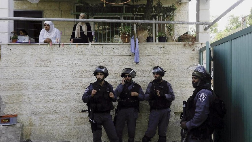 In this photo taken Tuesday, Sept. 30, 2014, Israeli police officers guard the entrance to the house of Ziad Qarain, that Jewish settlers moved into, at the Palestinian neighborhood of Silwan, East Jerusalem. The settlers say the home has been legally purchased, while Palestinian residents claim such sales are fraudulent. (AP Photo/Mahmoud Illean)
