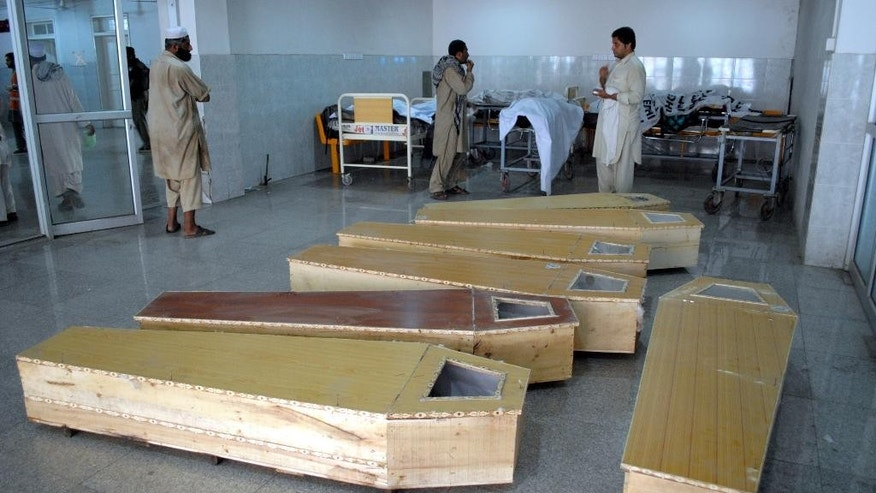 Pakistanis visit a mortuary following a blast in Peshawar, Pakistan, Thursday, Oct. 2, 2014. A bomb ripped through a mini-bus in northwestern Pakistan on Thursday, killing scores of passengers, police said. (AP Photo/Mohammad Sajjad)