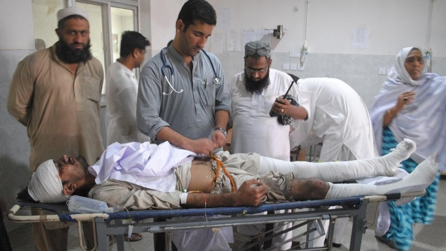 Pakistani doctors treat an injured victim of a bomb blast, at a local hospital in Peshawar, Pakistan, Thursday, Oct. 2, 2014. A bomb ripped through a mini-bus in northwestern Pakistan on Thursday, killing scores of passengers, police said. (AP Photo/Mohammad Sajjad)