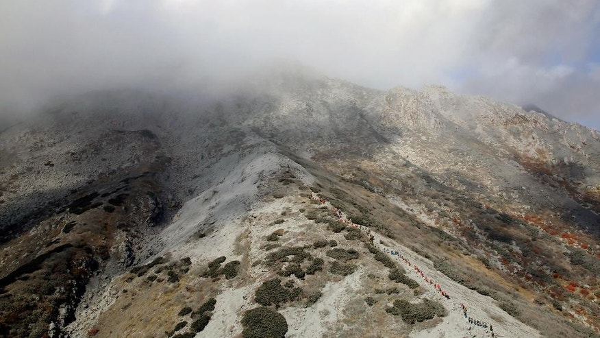 Rescuers, center, climb Mount Ontake covered by volcanic smoke and clouds for a search operation in central Japan, Thursday, Oct. 2, 2014. Saturday's eruption on Mount Ontake was the worst fatal eruption in postwar history in Japan. (AP Photo/Kyodo News) JAPAN OUT, MANDATORY CREDIT