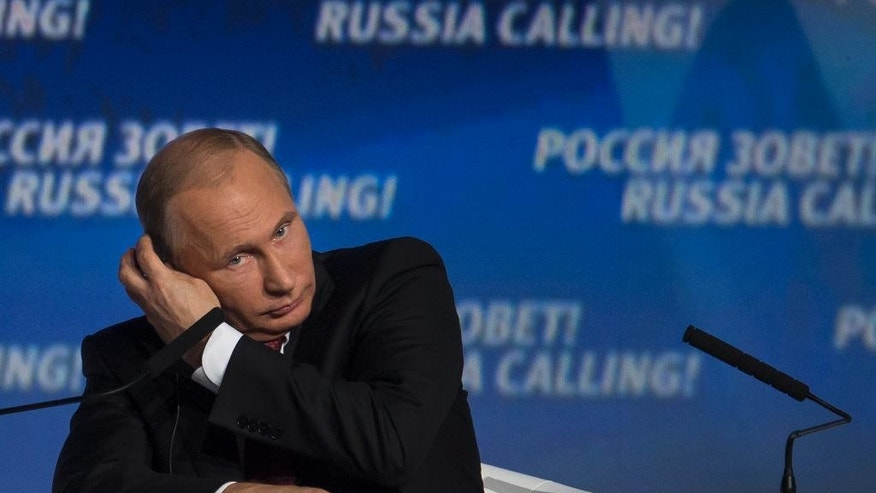 Russian President Vladimir Putin adjusts headphones during an investment conference Russia Calling in Moscow on Thursday, Oct. 2, 2014.  (AP Photo/Ivan Sekretarev)