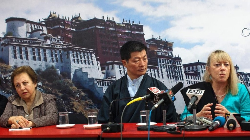 Lobsang Sangay, the elected leader of the Tibetan government-in-exile, flanked by Nobel peace laureates Iranian-born rights lawyer Shirin Ebadi, left and Liberian women's rights activist, Jody Williams address a press conference in Dharmsala, India, Wednesday, Oct.1, 2014. The Nobel peace laureates who were among those who skipped a meeting of Nobel peace laureates in South Africa on Oct. 13-15 are expected to meet the Dalai Lama on Thursday. (AP Photo/Ashwini Bhatia)