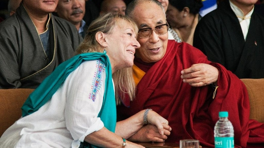 Tibetan spiritual leader the Dalai Lama, right, speaks to Nobel Laureate Jody Williams as they attend an event in Dharmsala, India, Thursday, Oct. 2, 2014. The event was organized to mark 25 years since the Dalai Lama was awarded the Nobel peace prize. Lobsang Sangay, prime minister of the Tibetan government-in-exile, is seated in background at right. (AP Photo/Ashwini Bhatia)