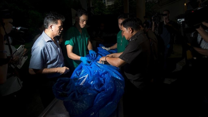 FILE - In this Tuesday, Sept. 16, 2014 file photo, the body of one of slain British tourists, Hannah Witheridge, wrapped in plastic sheet, is carried at a forensic police facility in Bangkok, Thailand. Police Maj. Gen. Kiattipong Khawsamang said Thursday, Oct. 2 that two out of three Myanmar workers questioned by police admitted murdering Witheridge, 23, and David Miller, 24. (AP Photo/Sakchai Lalit, File)