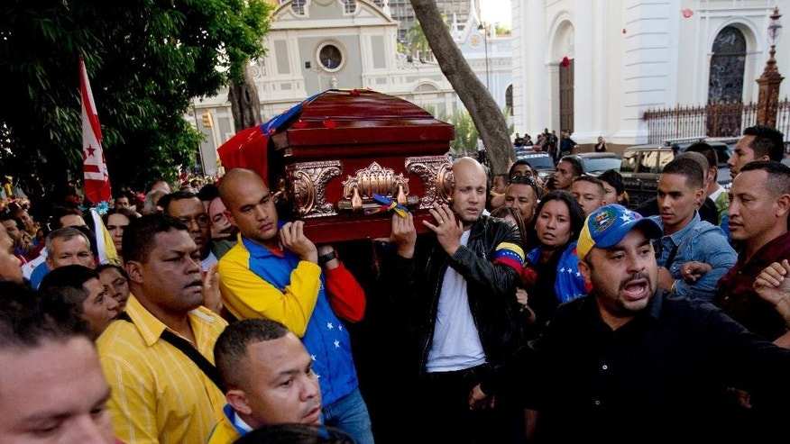 Venezuela's Education Minister Hector Rodriguez, left, and Sports Minister Antonio Alvarez, right, carry the coffin of the late lawmaker Robert Serra to the National Assembly in Caracas, Venezuela, Thursday, Oct. 2, 2014. Serra, a rising star in Venezuela's ruling socialist party, was stabbed to death in his home, officials said Thursday. The 27-year-old Serra was a lawyer by training and was elected to Congress in 2010 as a member of the ruling party. He gained prominence organizing youth to counter a wave of destabilizing student protests in 2007. (AP Photo/Fernando Llano)