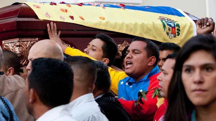 Supporters carry the coffin of slain lawmaker Robert Serra to the National Assembly for a public wake in Caracas, Venezuela, Thursday, Oct. 2, 2014. Serra, a rising star in Venezuela's ruling socialist party, was stabbed to death Wednesday in his home, officials said. The 27-year-old Serra was a lawyer by training and elected to Congress in 2010 as a member of the ruling party. He gained prominence organizing youth to counter a wave of destabilizing student protests in 2007. (AP Photo/Ariana Cubillos)