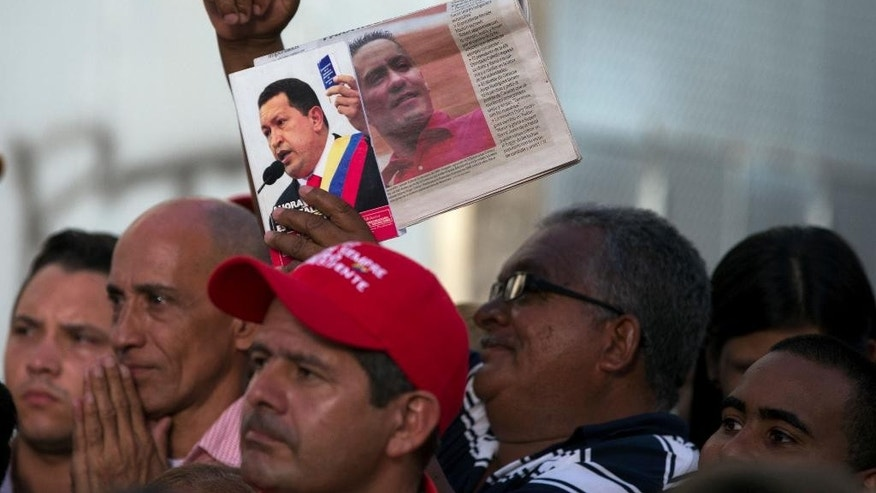 Supporters of slain Congressman Robert Serra hold up a picture of him, right, shown alongside a photo of Venezuela's President Hugo Chavez outside the National Assembly where Serra's body is brought for a public wake in Caracas, Venezuela, Thursday, Oct. 2, 2014.  Serra, a rising star in Venezuela's ruling socialist party, was stabbed to death in his home, officials said Thursday. The 27-year-old Serra was a lawyer by training and elected to Congress in 2010 as a member of the ruling party. He gained prominence organizing youth to counter a wave of destabilizing student protests in 2007. (AP Photo/Fernando Llano)