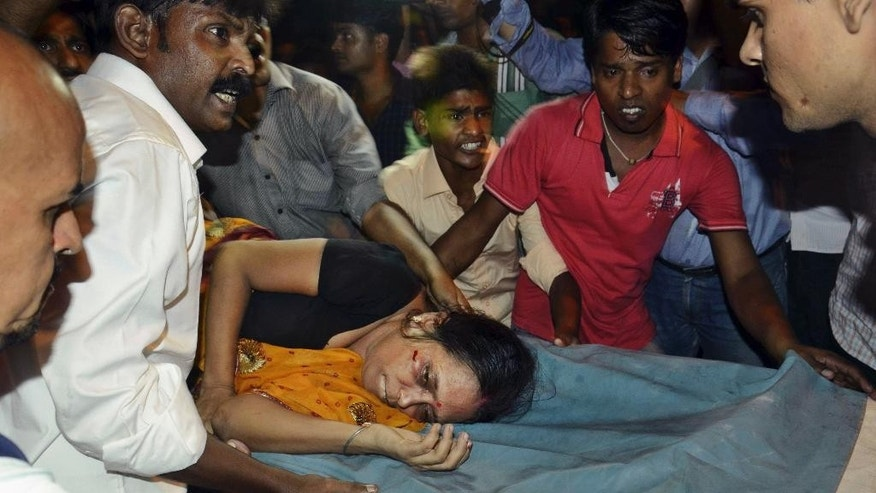 An Injured woman is carried on a stretcher to a hospital for treatment in Patna, India, Friday, Oct. 3, 2014. Officials say at least 25 died in a stampede during the religious festival of Dussehra in eastern India. (AP Photo/Aftab Alam Siddiqui)
