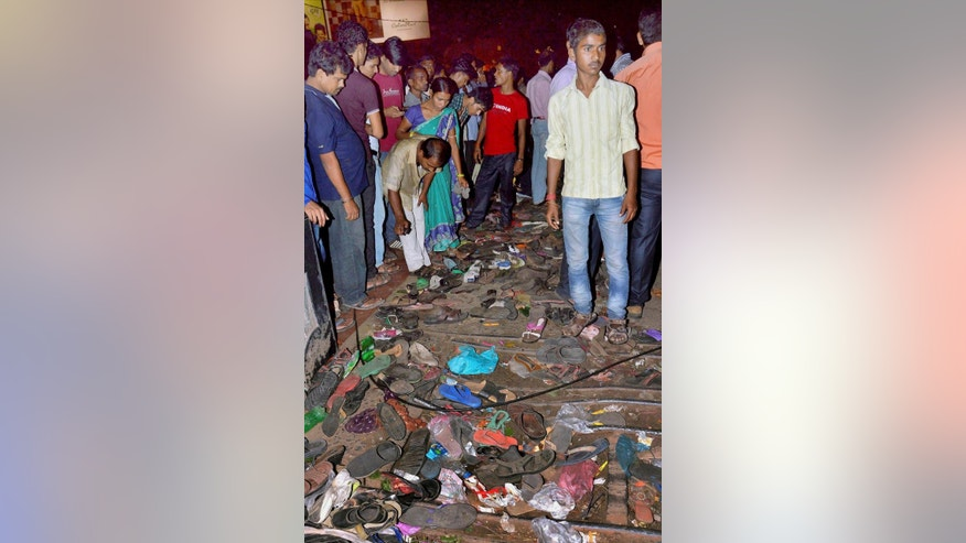 Footwear is scattered as Indians look at the stampede site in Patna, India, Friday, Oct. 3, 2014. Several people were killed Friday in a stampede in eastern India triggered by rumors that an electrical wire had fallen on people during a religious festival, an official said. (AP Photo/Press Trust of India) INDIA OUT