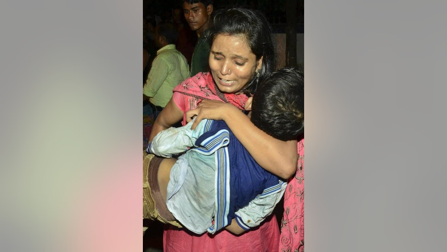 An unidentified woman carries the body of a boy killed in a stampede during Dussehra festival celebrations in Patna, India, Friday, Oct. 3, 2014. Atleast 32 people were killed and several injured in the stampede, according to Press Trust of India. (AP Photo/Aftab Alam Siddiqui)