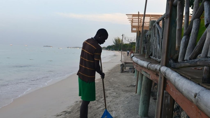 "In this Sept. 14, 2014 photo, John Beckford rakes a small area of sand separating the Lazy Dayz beach cottages from the Caribbean Sea in Negril, western Jamaica. Tourists from around the world are drawn to a stretch of palm-fringed shoreline known as ""Seven Mile Beach,"" a crescent of white sand along the turquoise waters of Jamaica's western coast. But, the sands are slipping away and Jamaicans fear the beach, someday, will need a new nickname. (AP Photo/David McFadden)"