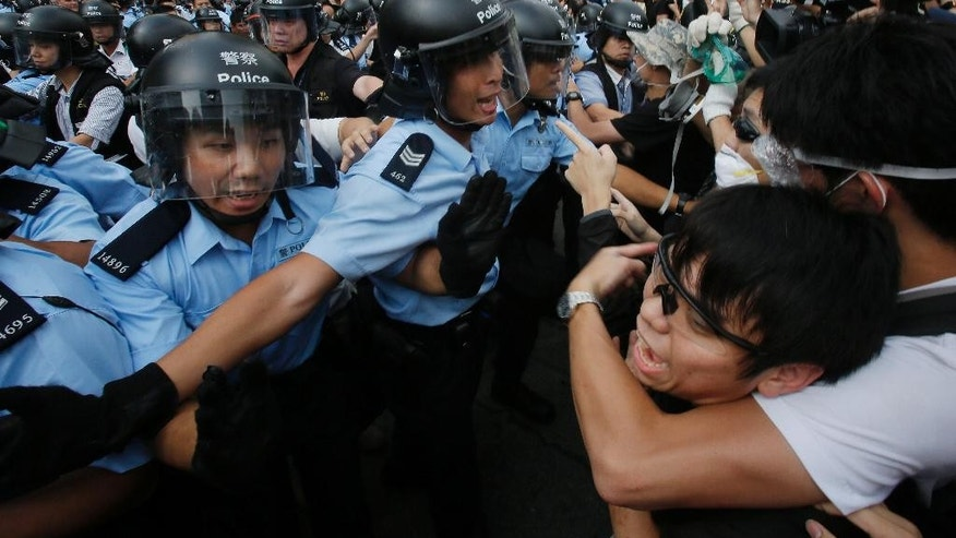 A pro-democracy student protester, left, is pressed by angry locals trying to remove the barricades blocking streets in Causeway Bay, Hong Kong, Friday, Oct. 3, 2014. Hong Kong protest leaders on Friday welcomed an offer by the territory's leader of talks to defuse the crisis over demonstrations seeking democratic reforms, though they continued to demand he resign and maintained barricades around government headquarters, frustrating staff going to work. (AP Photo/Wally Santana)