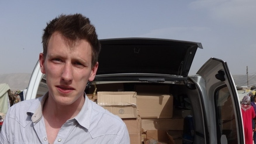 This undated photo provided by Kassig Family shows Peter Kassig standing in front of a truck filled with supplies for Syrian refugees. (AP/Kassig Family)