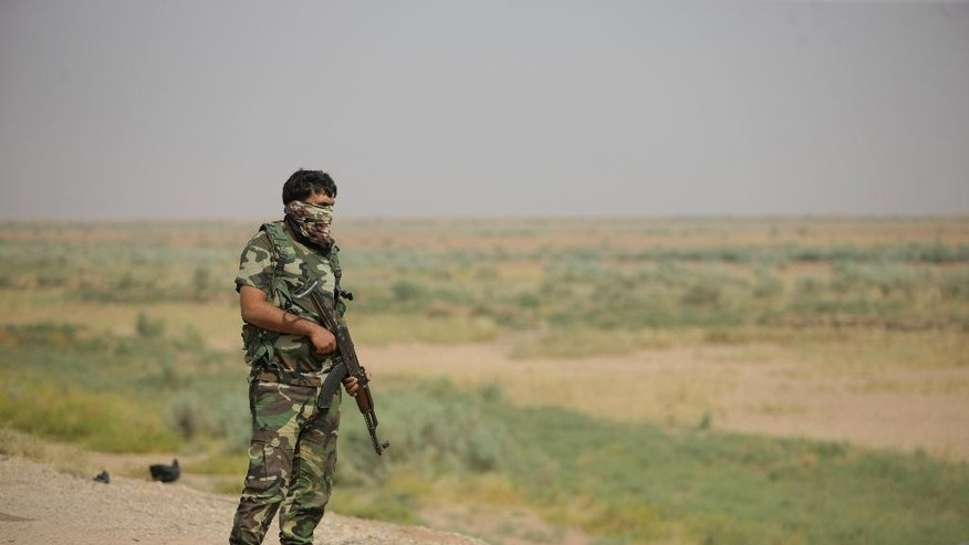 In this Thursday, Oct. 2, 2014 photo, an Iraqi Shiite militiamen stands alert after clashes with militants from the Islamic State group, near Qara Tappa, about 75 miles northeast of Baghdad in Iraq's Diyala province. (AP Photo/Jaber al-Helo)