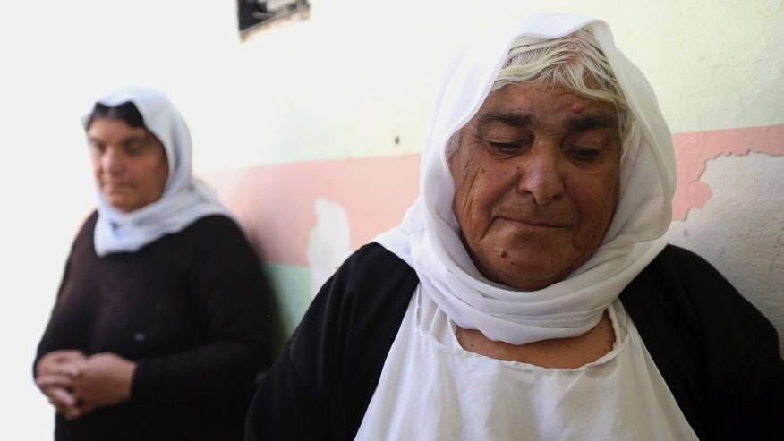 Aisha Ali Dirbou, about 70-year-old Yazidi who fled from Mosul, Iraq, after advances by Islamic militants take shelter at a school in Dahuk, 260 miles (420 kilometers) northwest of Baghdad, Thursday, Oct. 2, 2014. The Yazidis now living in the Kurdish city of Dahuk are cautiously optimistic - wary after having already lost so much, but hopeful to return home and pick up the pieces, as the Kurdish military says it is now on a push toward Sinjar, located in the deserts of northwestern Iraq near the Syrian border, in an assault aimed at retaking the town from the extremists. (AP Photo/Hadi Mizban)