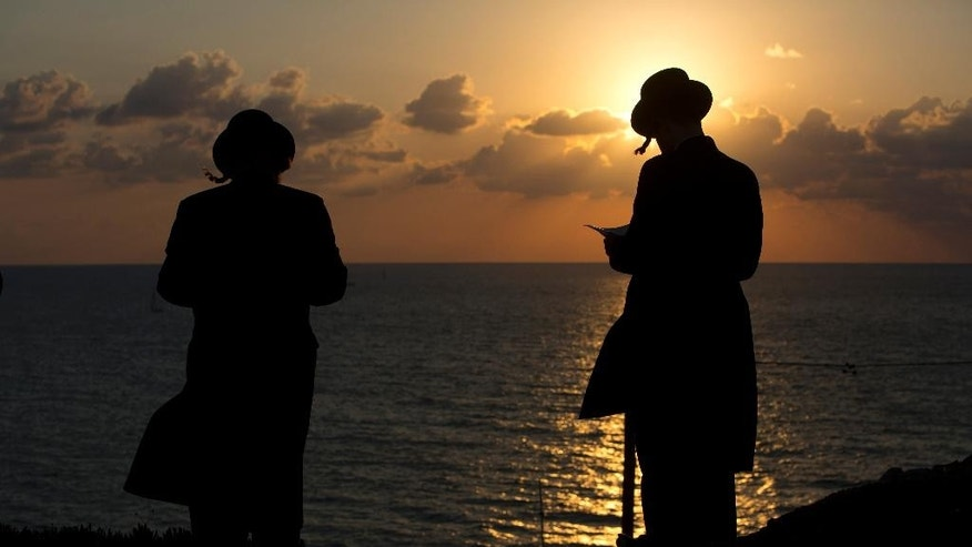 "Ultra-Orthodox Jews of the Hassidic sect Vizhnitz gather on a hill overlooking the Mediterranean sea as they participate in a Tashlich ceremony in Herzeliya, Israel, Thursday, Oct. 2, 2014. Tashlich, which means ""to cast away"" in Hebrew, is the practice by which Jews go to a large flowing body of water and symbolically ""throw away"" their sins by throwing a piece of bread, or similar food, into the water before the Jewish holiday of Yom Kippur, which start on Friday. (AP Photo/Oded Balilty)"