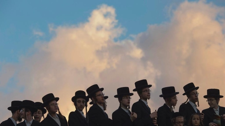 "Ultra-Orthodox Jews pray on the Hayarkon river bank during a Tashlich ceremony in the Israeli town of Ramat Gan near Tel Aviv, Israel, Thursday, Oct. 2, 2014. Tashlich, which means ""to cast away"" in Hebrew, is the practice by which Jews go to a large flowing body of water and symbolically ""throw away"" their sins by throwing a piece of bread, or similar food into the water before the Jewish holiday of Yom Kippur, which starts at sundown Friday. (AP Photo/Ariel Schalit)"