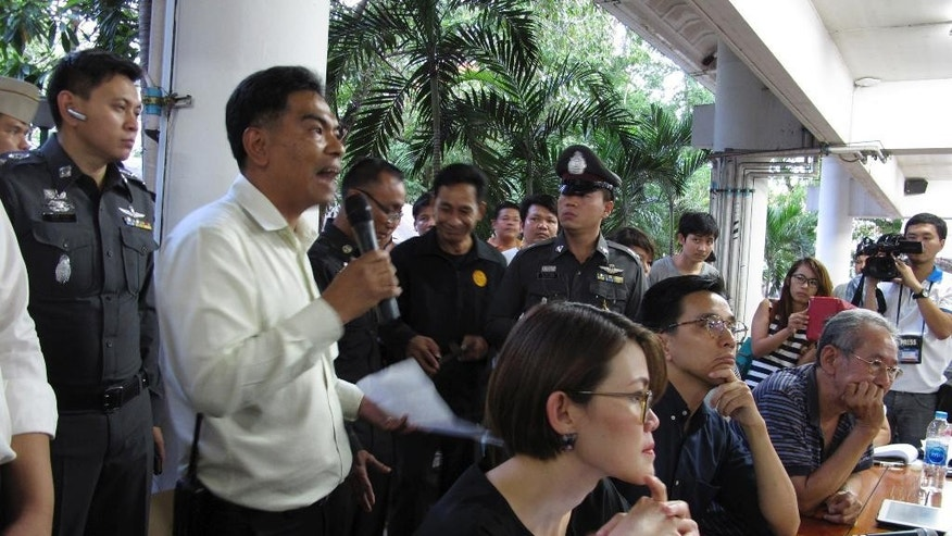 In this Sept. 18, 2014 photo, lecturers and panelists, Janjira Sombutpoonsiri, sitting left, Prajak Kongkirati, sitting at center, and Nidhi Eoseewong, sitting at right, listen to an announcement by an unidentified university official, accompanied by police officers, about the cancellation of an ongoing academic seminar held on the campus of Thammasat University in Pathum Thani, Thailand. Two days earlier, an army regiment asked the university for its cooperation to cancel the event to prevent divisiveness in the country. Since overthrowing an elected government in May, this nation's military rulers have jailed opponents who dared speak out and silenced the rest with the threat of prosecution. They have censored the media, dispersed protesters and forbidden open debate over the nation's fate. (AP Photo/Thanyarat Doksone)