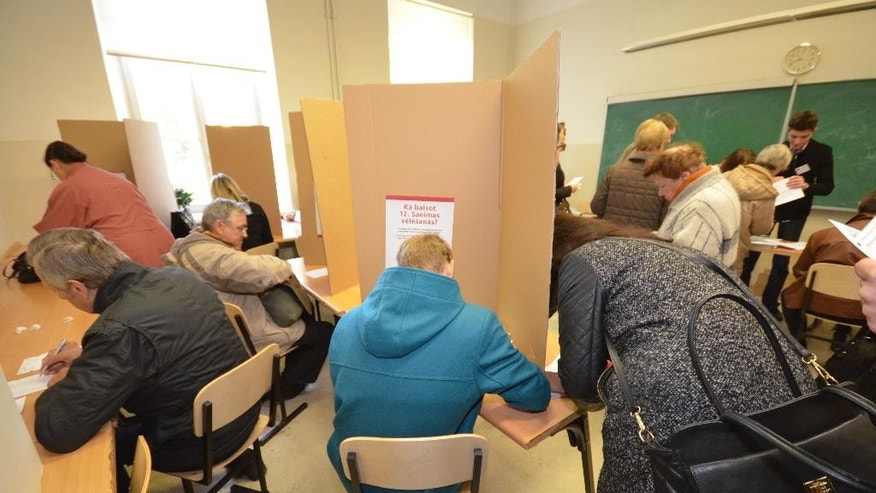 Latvian voters cast advance ballots at a high school in Riga on Thursday, Oct. 2, 2014. The Baltic country is holding a Parliamentary election on Oct. 4, amid worries over Russia's intervention in Ukraine. (AP Photo/Tor Bernhard Slaathaug)