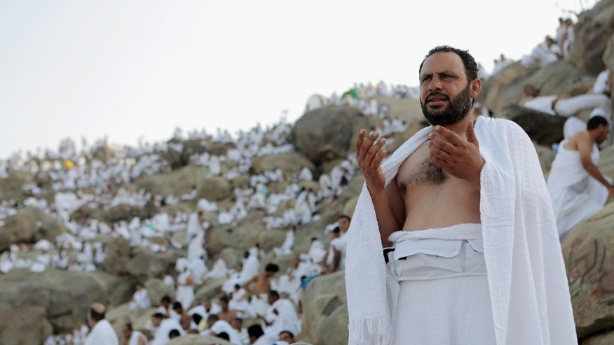 Muslim pilgrims pray at Jabal Al Rahma holy mountain, or the mountain of forgiveness, during the annual pilgrimage, known as the hajj, near Mecca, Saudi Arabia, Friday, Oct. 3, 2014. An estimated 2 million Muslims are streaming into a sprawling tent city near Mecca for the annual hajj pilgrimage. Saudi Arabia banned hajj and work visas this year for people from Sierra Leone, Liberia and Guinea as a precaution to avoid the spread of Ebola during hajj, which sees massive crowds of people from around the world gather in Mecca. (AP Photo/Khalid Mohammed)