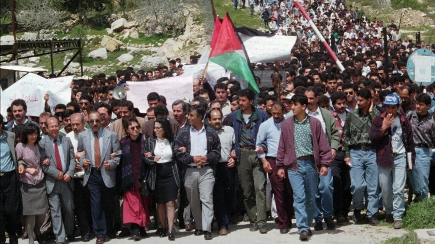 FILE - In this April 1, 1996 file photo, Palestinian protesters march from the Bir Zeit University in the West Bank. The expulsion of an Israeli journalist on Sept. 23, 2014, from an academic conference hosted by a top Palestinian university has unleashed a fierce debate about academic freedom in the West Bank and is shining a spotlight on the apparent radicalization of some young Palestinians who are disillusioned by years of failed peace efforts and have grown up with little contact with Israelis. (AP Photo/Sanad Sahlieh, File)