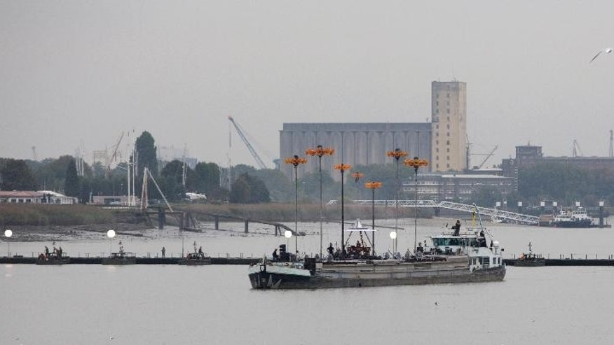 Belgian and Dutch army engineers work on a floating pontoon bridge over the River Scheldt in Antwerp, Belgium on Thursday, Oct. 2, 2014. Antwerp will open it's World War I Centenary program in Oct. 3, 2014 with the pontoon bridge and allow the general public to cross it. The pontoon bridge is an actual reconstruction of the original that spanned the River Scheldt at the start of the war in 1914 and played a major role in the defense of Antwerp. It was used by the Belgian army under King Albert I as well as the British Expeditionary Force under Winston Churchill. (AP Photo/Virginia Mayo)
