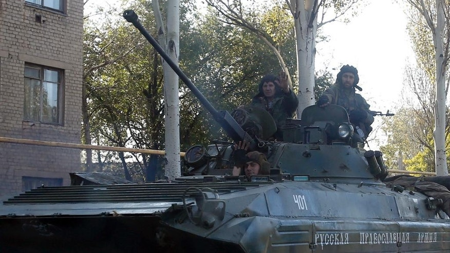 "An  pro-Russian rebel armored personal carrier with an inscription reading: ""Russian Orthodox Christian Army"" passes through the town of Donetsk, eastern Ukraine, Thursday, Oct. 2, 2014. Pro-Russian rebels in eastern Ukraine advanced Wednesday on the government-held airport in Donetsk, pressing to seize the key transportation hub even as the two sides bargained over a troop pullout under a much-violated truce. (AP Photo/Darko Vojinovic)"