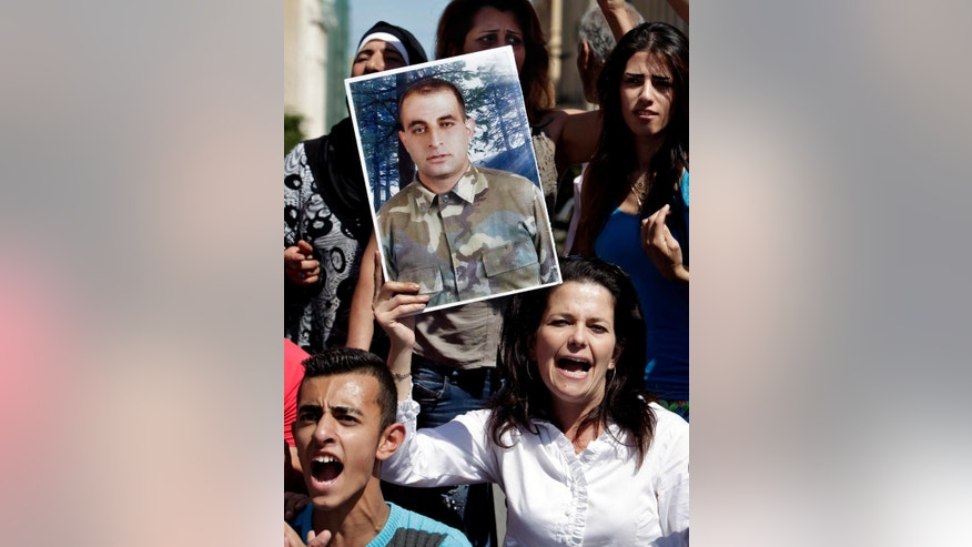 Relatives of missing Lebanese soldier Saif Thebian, who was kidnapped by Islamic State militants and the Al-Nusra front, chant slogans as they hold his portrait, during a demonstration to demand action to secure the captives release, in front the Lebanese government building, in downtown Beirut, Lebanon, Thursday, Oct. 2, 2014. Militants, including from the Islamic State extremist group, seized around 30 soldiers and policemen after overrunning a Lebanese border town in early August. (AP Photo/Bilal Hussein)