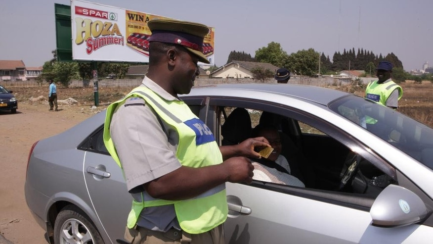 "A police officer smiles while inspecting a motorist licence in Harare, Friday, Oct. 3, 2014 on World Smile Day.  According to  Zimbabwe's deputy Minster of Home Affairs Ziyambi Ziyambi whose ministry is in charge of the police, the hospitality agency would conduct ""smiling""  training sessions to make the law enforcers friendlier towards tourists and motorists. (AP Photo/Tsvangirayi Mukwazhi)"