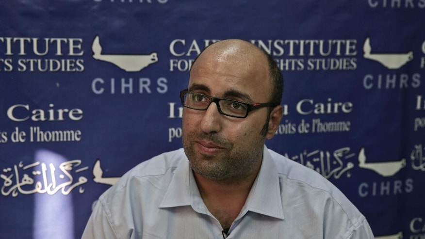 "In this Tuesday, Sept. 30, 2014 photo, Mohammed Zaree, the Egyptian Program Manager for the Cairo Institute for Human Rights Studies, speaks during an interview with The Associated Press at his office in Cairo, Egypt. ""Operating under the current law is impossible,"" said Zaree. The deadline ""is in essence an effort to shut down the public sphere in Egypt. The current administration is showing that it has zero tolerance for any critical voices."" (AP Photo/Nariman El-Mofty)"