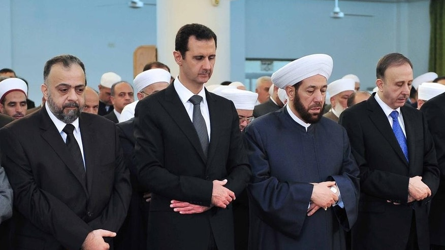 In this photo released by the Syrian official news agency SANA, Syrian President Bashar Assad, second left, prays during Eid al-Adha prayer at a mosque in Damascus, Syria, on Saturday Oct. 4, 2014. Assad has made a rare public appearance by attending prayers at a mosque in the capital, marking the beginning of the important Muslim holiday. (AP Photo/SANA)