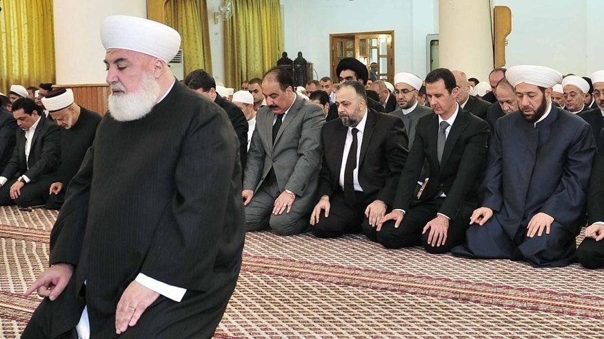 In this photo released by the Syrian official news agency SANA, Syrian President Bashar Assad, background second right, prays during Eid al-Adha prayer at a mosque in Damascus, Syria, Saturday Oct. 4, 2014. Assad has made a rare public appearance by attending prayers at a mosque in the capital, marking the beginning of the important Muslim holiday. (AP Photo/SANA)