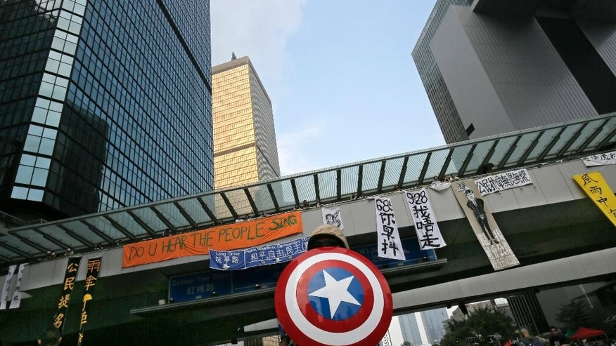 A protester carries a shield from the Captain America comic during a rally outside government headquarters one day after protesters were threatened by residents and pro-Beijing supporters in Kowloon's crowded Mong Kok district Saturday, Oct. 4, 2014 in Hong Kong. Police arrested 19 people, some believed to have organized crime ties, during a night of running brawls stretching into Saturday as mobs tried to drive pro-democracy protesters from the streets where they've held a weeklong, largely peaceful demonstration.  (AP Photo/Vincent Yu)