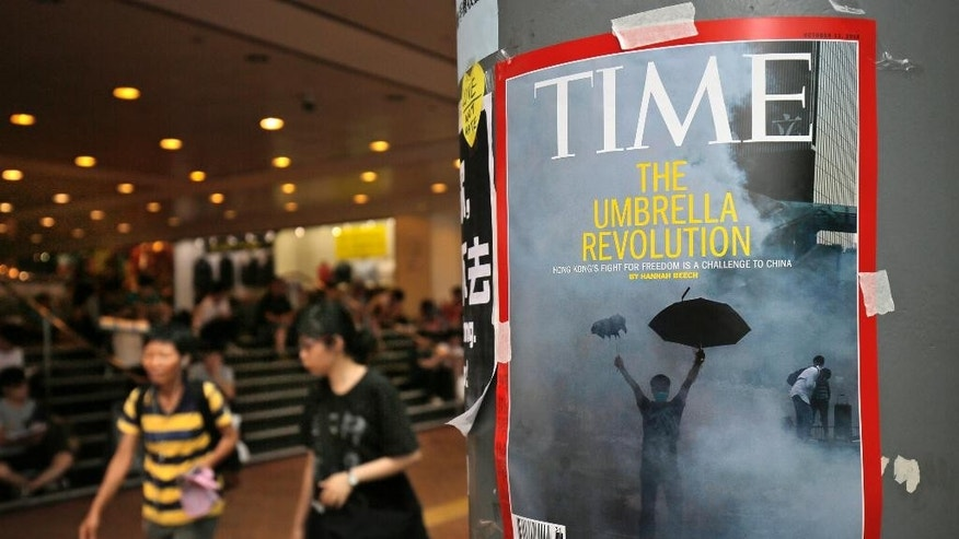 A cover of Time Magazine is taped to a pole during a rally outside government headquarters one day after protesters were threatened by residents and pro-Beijing supporters in Kowloon's crowded Mong Kok district Saturday, Oct. 4, 2014, in Hong Kong. Police arrested 19 people, some believed to have organized crime ties, during a night of running brawls stretching into Saturday as mobs tried to drive pro-democracy protesters from the streets where they've held a weeklong, largely peaceful demonstration.  (AP Photo/Vincent Yu)