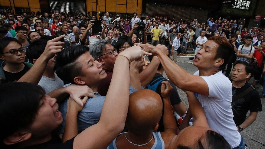 Pro-democracy student protesters confront local residents in Mong Kok, Hong Kong, Saturday, Oct. 4, 2014. Friction between pro-democracy protesters and opponents of their weeklong occupation of major Hong Kong streets persisted Saturday as police denied they had any connection to criminal gangs suspected of inciting attacks on largely peaceful demonstrators. (AP Photo/Wally Santana)
