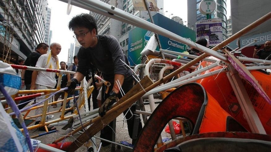 Pro-democracy student protesters strengthen their makeshift barriers around their encampment in Mong Kok, Hong Kong, Saturday, Oct. 4, 2014. Friction between pro-democracy protesters and opponents of their weeklong occupation of major Hong Kong streets persisted Saturday as police denied they had any connection to criminal gangs suspected of inciting attacks on largely peaceful demonstrators. (AP Photo/Wally Santana)