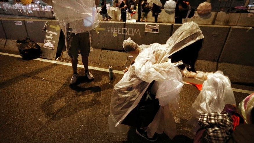 Student pro-democracy protesters move their belongings out of the rain after spending the night on the streets near government headquarters, Sunday, Oct. 5, 2014 in Hong Kong. Pro-democracy protesters were defiant in the face of attacks by opponents and warnings by the Hong Kong government to clear the streets, staging a massive rally Saturday evening in the downtown business district they've occupied for a week. (AP Photo/Wong Maye-E)