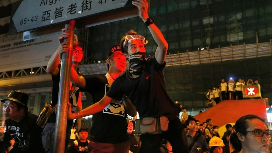 Pro-democracy student protesters stage a rally on a occupied road in Mongkok district, Hong Kong, Sunday, Oct. 5, 2014. Pro-democracy protesters were defiant in the face of attacks by opponents and warnings by the Hong Kong government to clear the streets, staging a massive rally Saturday evening in the downtown business district they've occupied for a week. (AP Photo/Kin Cheung)