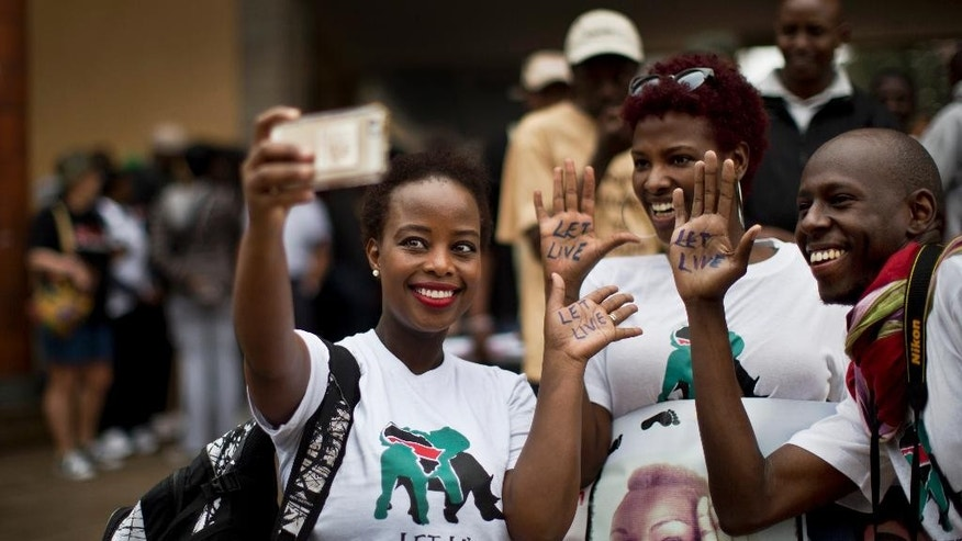 "Demonstrators take a ""selfie"" with their smartphone and display the message ""Let Live"" on the palms of their hands as they take part in the ""Global March for Elephants and Rhinos"" to raise awareness for their plight, in Nairobi, Kenya Saturday, Oct. 4, 2014. Organisers of the global march, which they hope will take place in over 100 cities across the world, say it is a collaboration between many wildlife conservation organisations aiming to save elephants and rhinos from extinction by poachers and call for a ban on the trade of ivory and rhino horn. (AP Photo/Ben Curtis)"